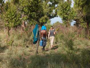 Hiking through the forest to the river with Mursi man